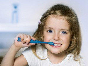 Child girl cleaning teeth with toothbrush in the bathroom.